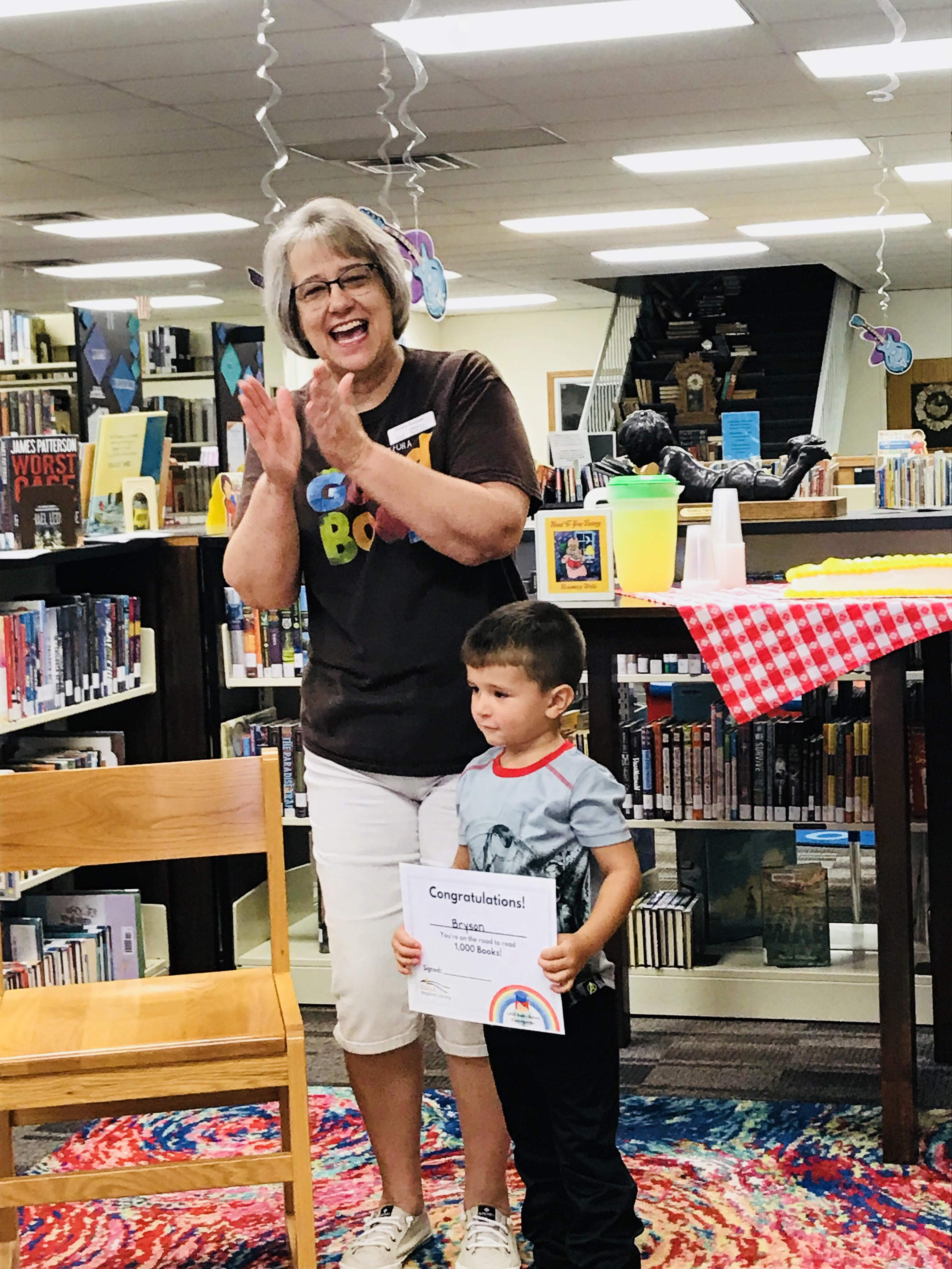 librarian clapping for child holding reading certificate