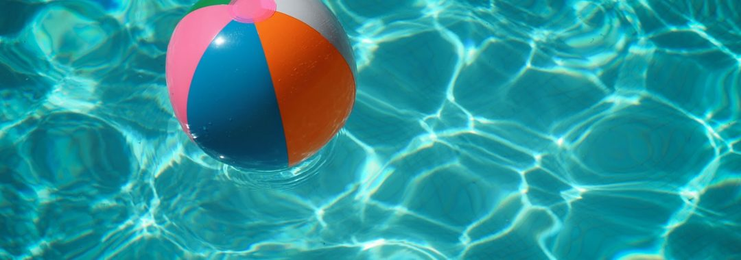 multicolor beach ball floating in pool